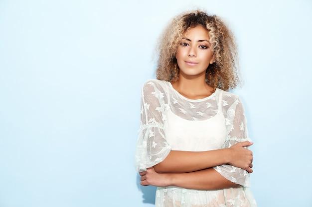 Lächelnde modellfrau in den trendigen sommerkleidern posiert