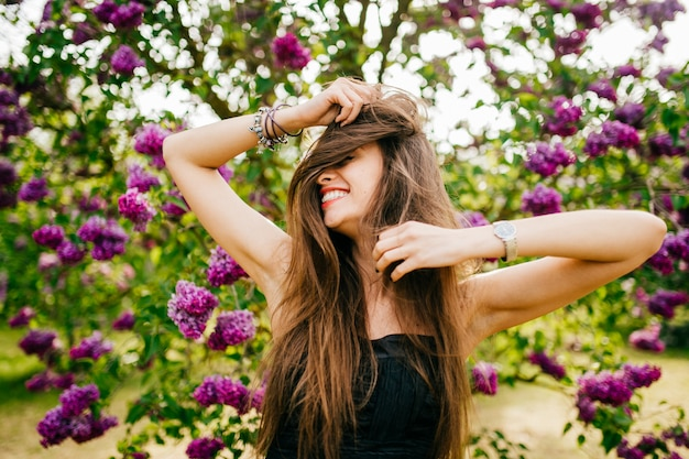 Lächelnde modellfrau mit langen haaren im sommerfliedergarten