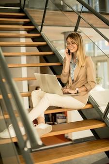 Lächelnde moderne geschäftsfrau, die auf der treppe im büro sitzt, am notizbuch arbeitet und auf handy spricht