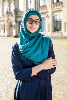 Lächelnde moslemische junge geschäftsfrau im hijab. glückliche arabische studentin mit gläsern. schöne islamische frau.