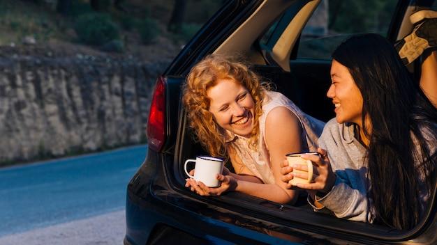 Lächelnde multiethnische junge frauen, die im offenen autokofferraum sprechen