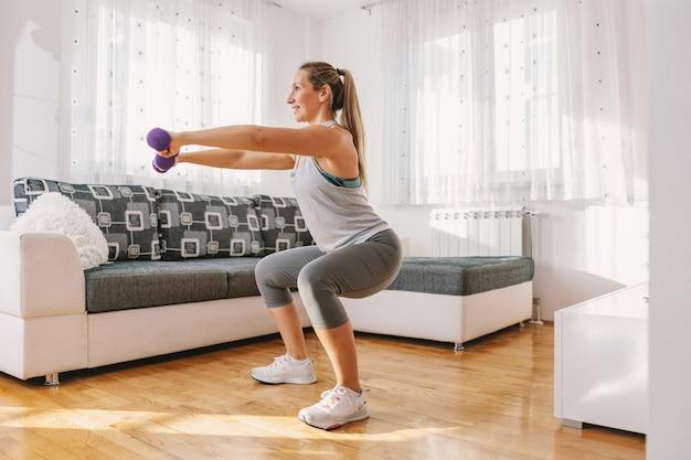 Lächelnde muskulöse sportlerin in form kniebeugen und hanteln halten.