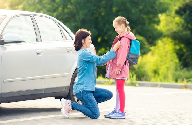 Lächelnde mutter bringt tochter zurück zur schule und verabschiedet sich auf dem parkplatz