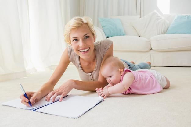 Lächelnde mutter des porträts mit ihrem baby, das auf ein schreibheft schreibt