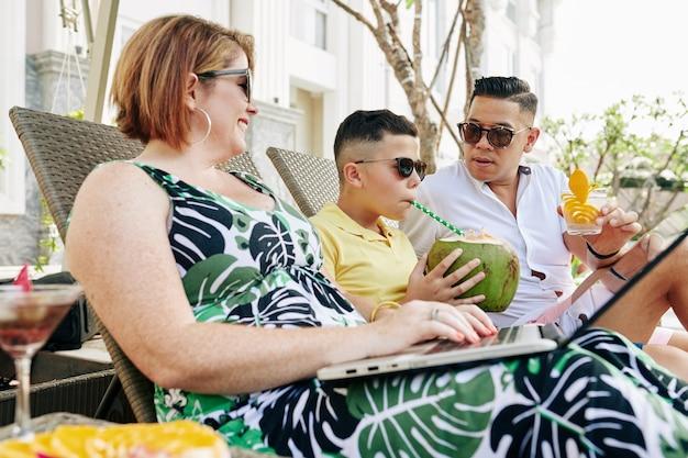 Lächelnde mutter, die am laptop arbeitet, vater, der gin trinkt, und ihr sohn, der kokosnusscocktail zum ersten mal trinkt, wenn familie am pool ruht