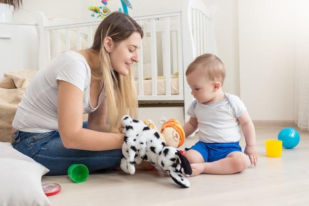 Lächelnde mutter, die eine hundepuppe zur hand trägt und mit ihrem baby spielt