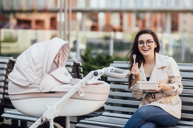 Lächelnde mutter, die eine plastik-lunchbox hält, während sie mit kinderwagen und neugeborenem auf einer bank sitzt