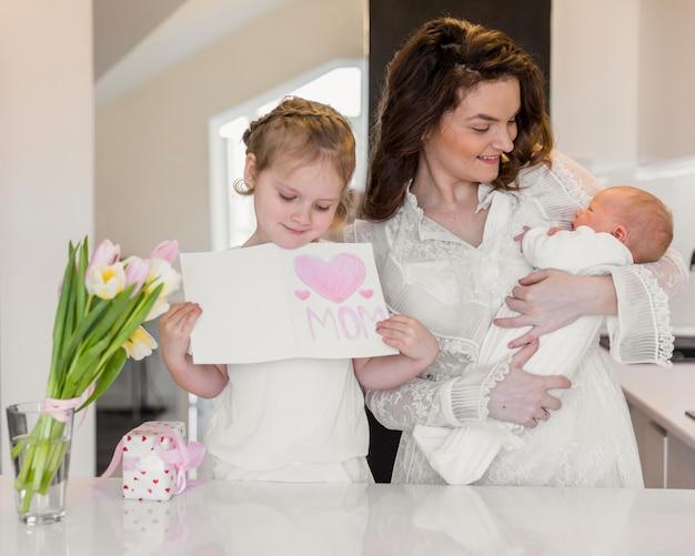 Lächelnde mutter, die ihr baby während tochter hält grußkarte trägt