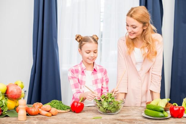 Lächelnde mutter, die ihre tochter zubereitet salat in der glasschüssel auf holztisch betrachtet
