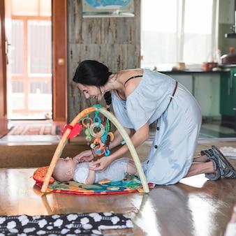 Lächelnde mutter, die mit ihrem baby liegt auf sich entwickelnder wolldecke mit beweglichen pädagogischen spielwaren spielt