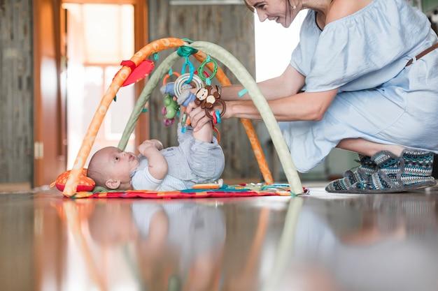 Lächelnde mutter, die mit ihrem baby liegt auf sich entwickelnder wolldecke über dem reflektierenden boden spielt