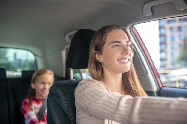 Lächelnde mutter, die mit ihrer tochter fährt, die auf rücksitz des autos sitzt
