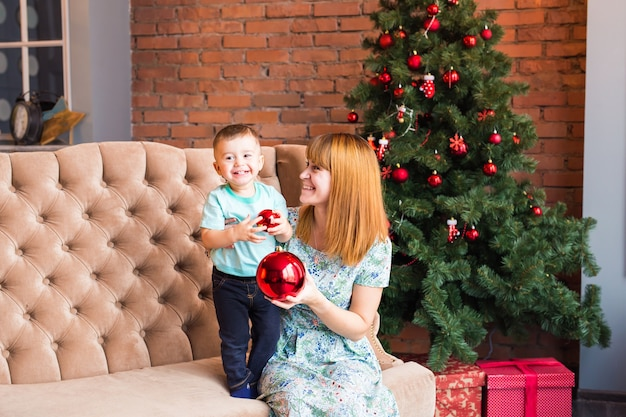 Lächelnde mutter, die mit reizendem niedlichen kleinen sohn nahe weihnachtsbaum spielt