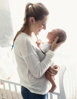 Lächelnde mutter, die sich an den händen hält und ihr baby anschaut