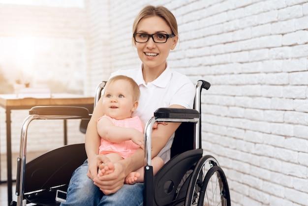 Lächelnde mutter im rollstuhl, der neugeborenes baby umarmt.