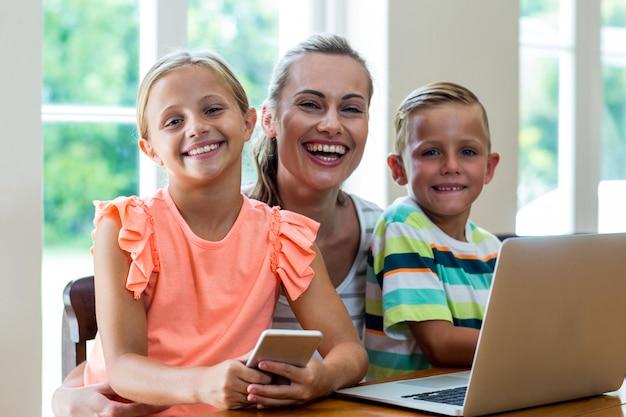 Lächelnde mutter mit den kindern, die technologien halten