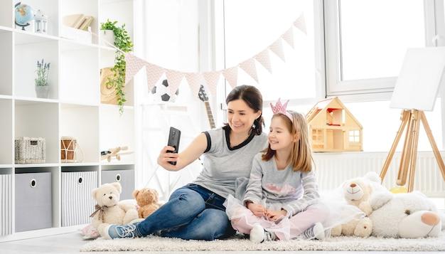Lächelnde mutter mit tochter, die selfie im süßen kinderzimmer macht