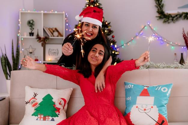 Lächelnde mutter mit weihnachtsmütze hält wunderkerzen