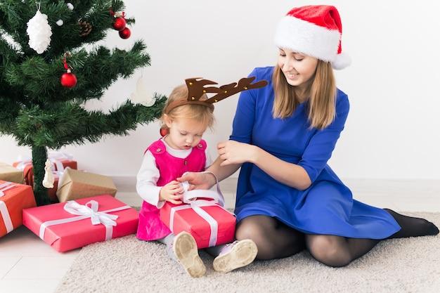 Lächelnde mutter öffnen weihnachtsgeschenke mit der kleinen tochter im zimmer