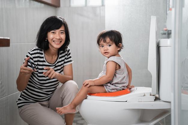 Lächelnde mutter und baby schauen in die kamera, während sie videos auf mobiltelefonen auf der toilette im badezimmer ansehen
