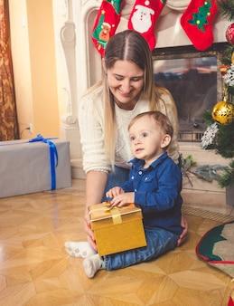 Lächelnde mutter und ihr kleiner sohn mit weihnachtsgeschenk auf dem boden im wohnzimmer
