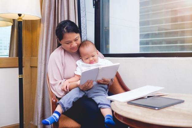 Lächelnde mutter und ihr nettes kleines asiatisches 18 monate / 1 einjahreskleinkindbabykind-lesebuch, zu hause sitzend auf stuhl