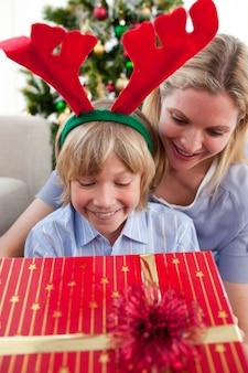 Lächelnde mutter und ihr sohn, die weihnachtsgeschenk öffnen