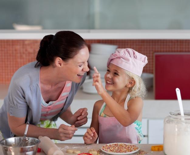 Lächelnde mutter und ihre tochter, die in einer küche backen