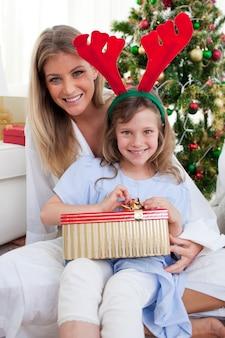 Lächelnde mutter und ihre tochter, die weihnachtsgeschenke auspacken