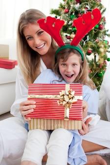 Lächelnde mutter und ihre tochter, die weihnachtsgeschenke öffnen