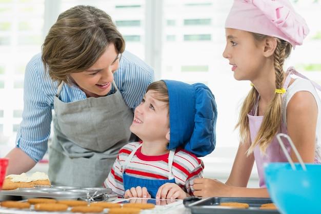 Lächelnde mutter und kinder interagieren miteinander, während sie kekse vorbereiten