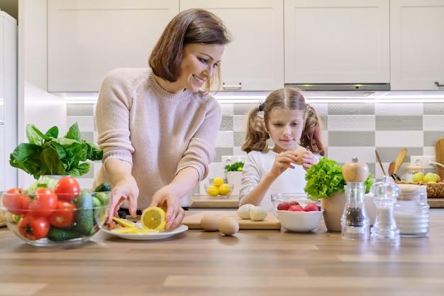 Lächelnde mutter und tochter 8, 9 jahre alt, die zusammen in der küche kochen
