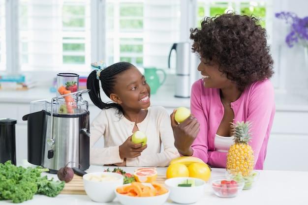 Lächelnde mutter und tochter bereiten erdbeersmoothie in der küche vor