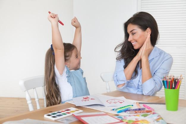Lächelnde mutter und tochter bereiten sich auf den unterricht vor und zeichnen mit bleistiften und farben am tisch
