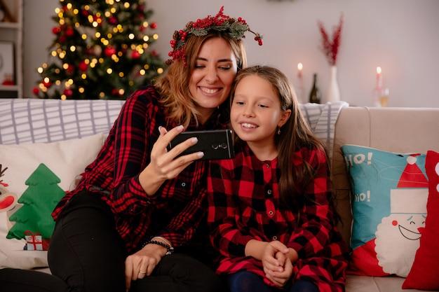 Lächelnde mutter und tochter, die auf das telefon schauen, das auf der couch sitzt und die weihnachtszeit zu hause genießt