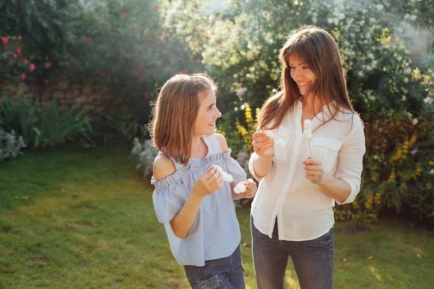 Lächelnde mutter und tochter, die eibischaufsteckspindel halten und einander im park betrachten