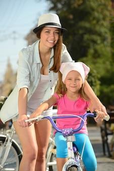 Lächelnde mutter und tochter, die ein fahrrad auf die straße reiten.