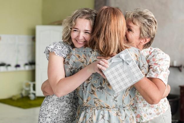 Lächelnde mutter und tochter, die ihre oma mit dem halten der geschenkbox umarmen
