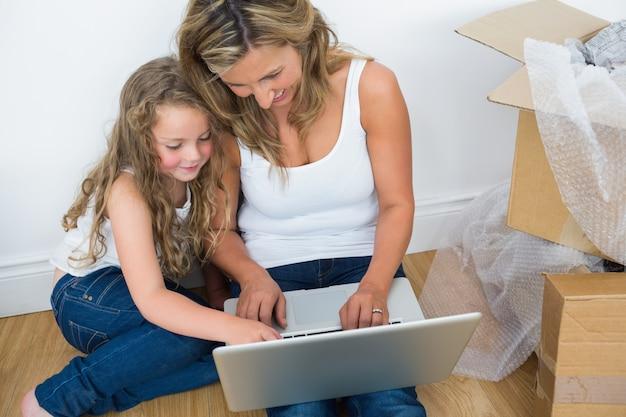Lächelnde mutter und tochter, die laptop verwendet