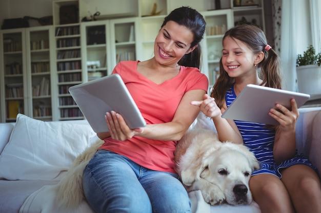 Lächelnde mutter und tochter, die mit haustierhund sitzen und digitales tablett verwenden