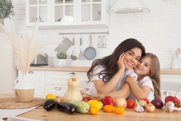 Lächelnde mutter und tochter, die obst und gemüse in der küche im skandinavischen stil kochen.
