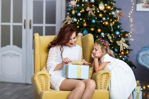 Lächelnde mutter und tochter mit geschenkbox