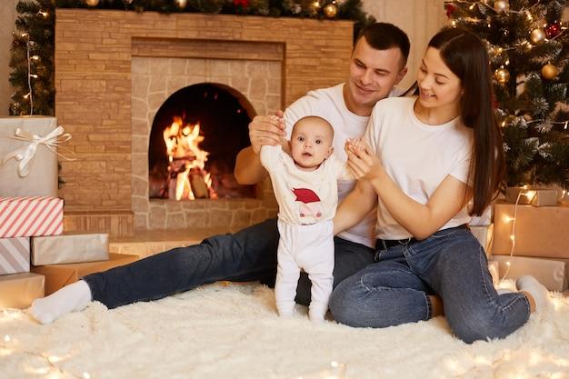 Lächelnde mutter und vater verbringen zeit zusammen mit ihrer kleinen tochter, während sie auf dem boden in der nähe von kamin und weihnachtsbaum sitzen, frohe weihnachten und ein glückliches neues jahr.
