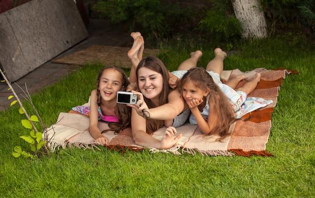 Lächelnde mutter und zwei töchter machen fotos von sich selbst im park