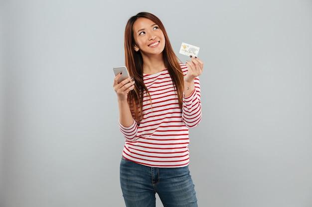Lächelnde nachdenkliche asiatische frau im pullover, der smartphone und kreditkarte über grauem hintergrund hält