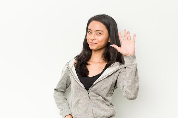 Lächelnde nette darstellende nr. fünf der chinesischen frau der jungen eignung mit den fingern.