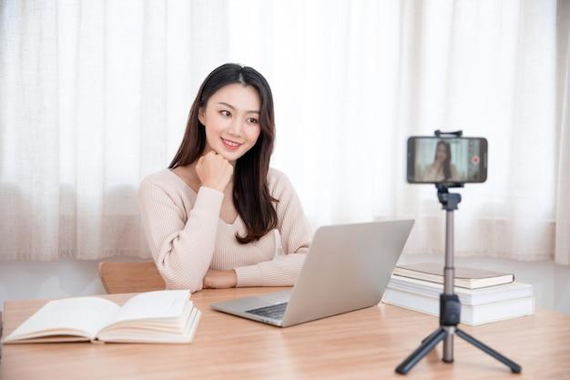 Lächelnde niedliche junge asiatische bloggerin, die video aufzeichnet