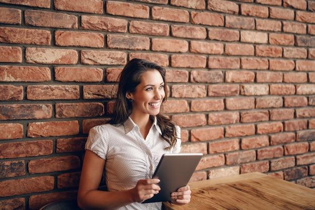 Lächelnde niedliche kaukasische brünette, die im café sitzt und tablette verwendet. im hintergrund backsteinmauer.