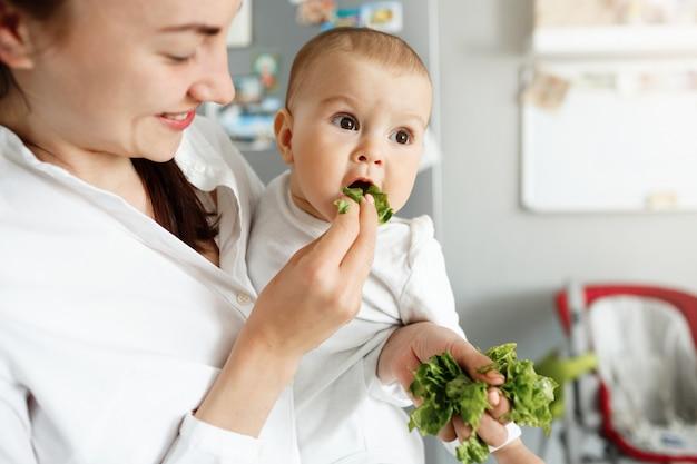 Lächelnde niedliche mutter, die baby mit salat füttert