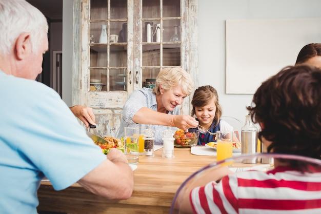 Lächelnde oma und enkelin beim sitzen am speisetische
